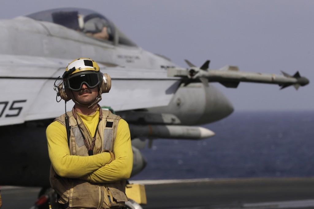 A crew member is seen on duty on the deck of the U.S. Navy USS Ronald Reagan in the South China Sea, Tuesday, Nov. 20, 2018. China is allowing a U.S.