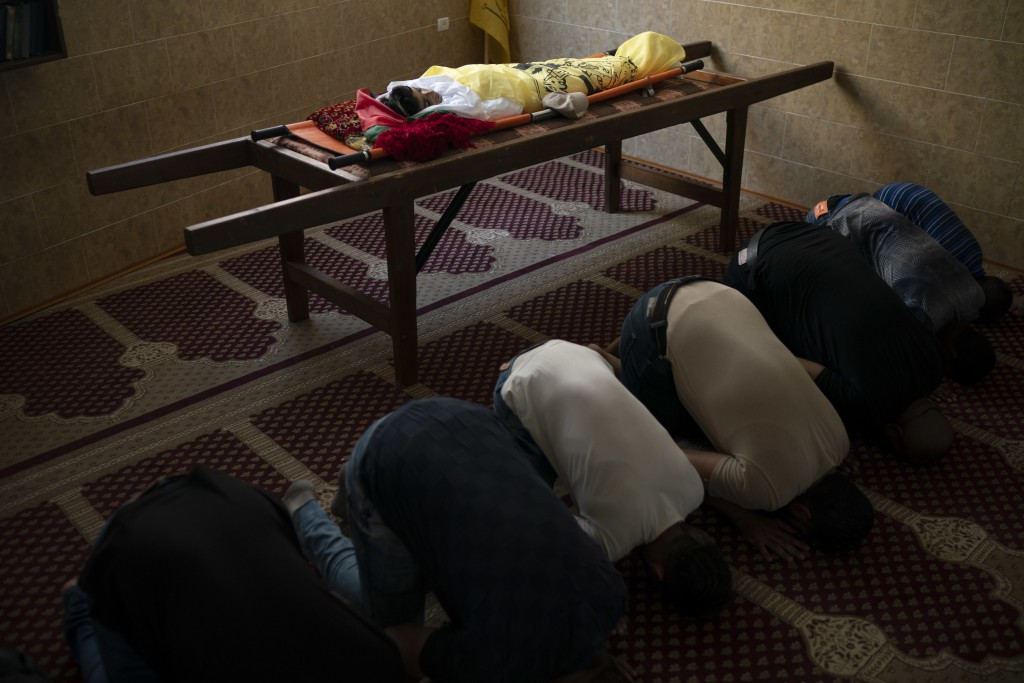 In this Sept. 15, 2018 photo, Palestinians pray next to the body of 11-year-old Shady Abdel-al during his funeral in Beit Lahiya, northern Gaza Strip....