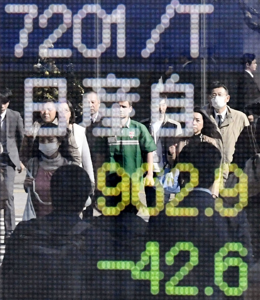 With passersby reflected on the electronic stock board, the stock price of Nissan Motor shows the day's loss, in green, at a securities firm in Tokyo,...
