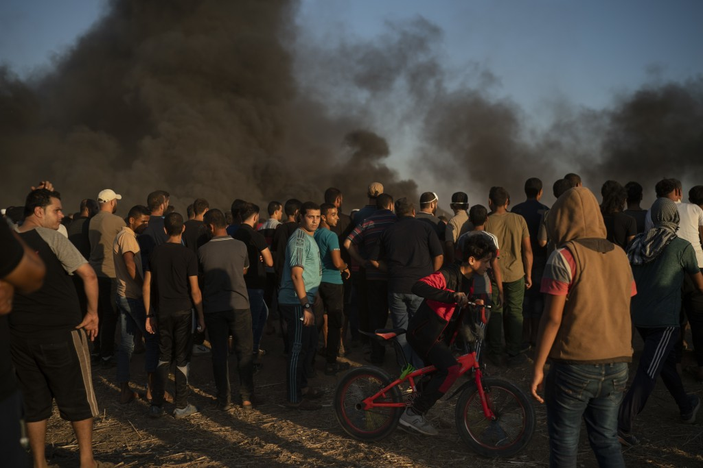 In this Friday, Sept. 14, 2018  photo, a boy rides his bike as Palestinians gather during a protest at the Gaza Strip's border with Israel, east of Ga...