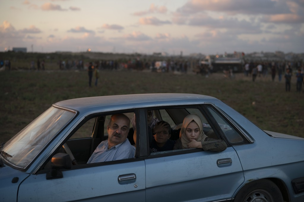 In this Friday, Sept. 14, 2018 photo, Khalil Ayesh sits in his car with his family watching Palestinian protesters at the Gaza Strip's border with Isr...