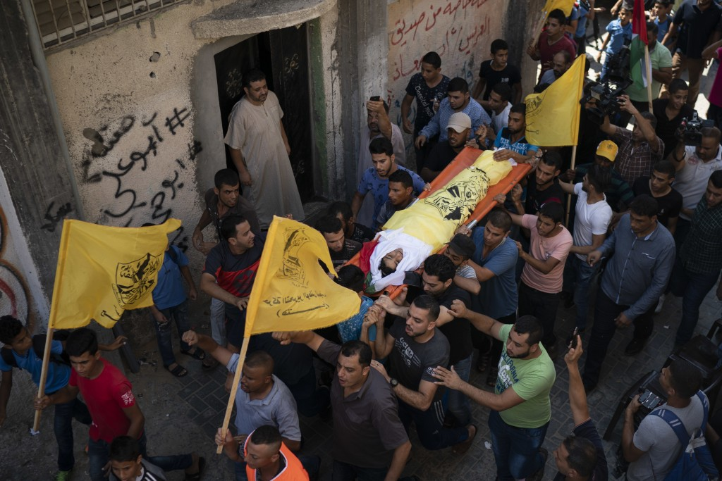 In this Sept. 15, 2018 photo, Palestinians carry the body of 11-year-old Shady Abdel-al during his funeral in Beit Lahiya, northern Gaza Strip. As the...