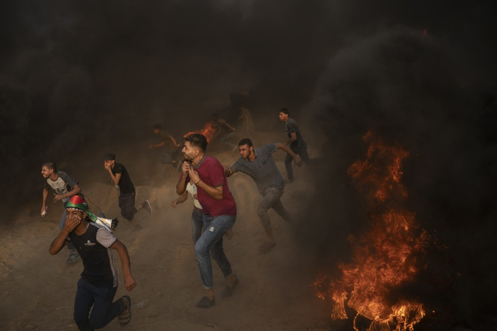 In this Friday, Aug. 31, 2018 photo, Palestinian protesters run from teargas fired by Israeli troops during a protest at the Gaza Strip's border with ...