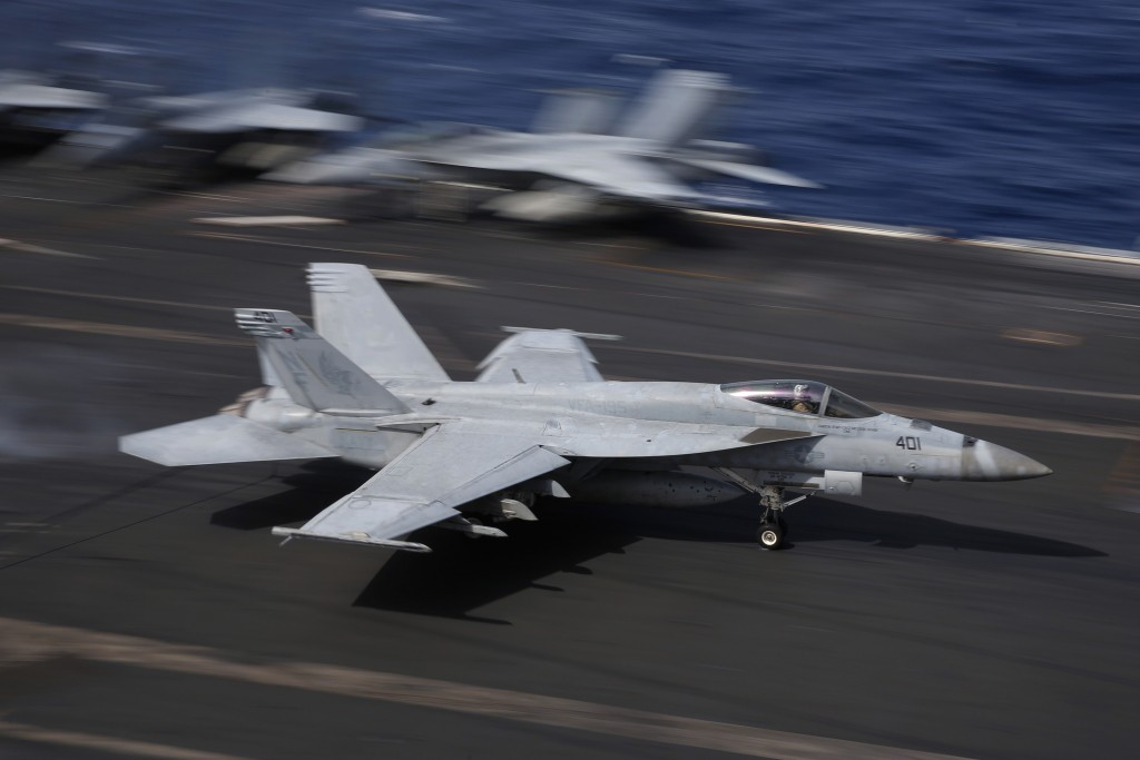 In this Nov. 20, 2018, photo, an F/A-18 Super Hornet fighter jet lands on the deck of the U.S. Navy USS Ronald Reagan in the South China Sea. China is