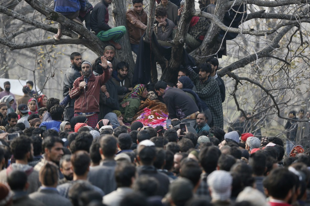 In this Nov. 20, 2018, photo,  an unidentified Kashmiri Muslim kisses the body of rebel Bashrat Ahmad during his funeral at Shopian, south of Srinagar...