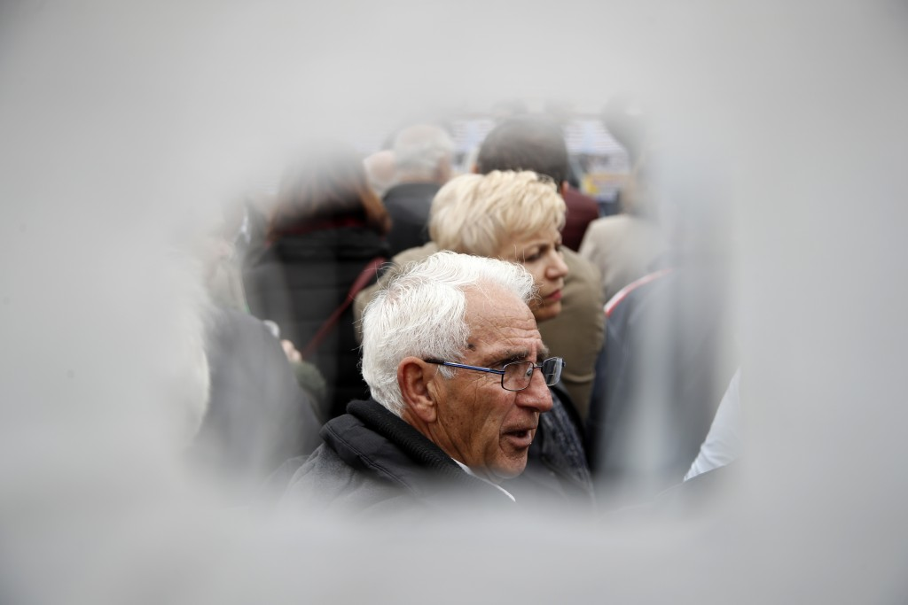 An elderly man  is photographed through a hole in a banner during a rally in Athens, Tuesday, Nov. 20, 2018. Hundreds of pensioners protested demandin