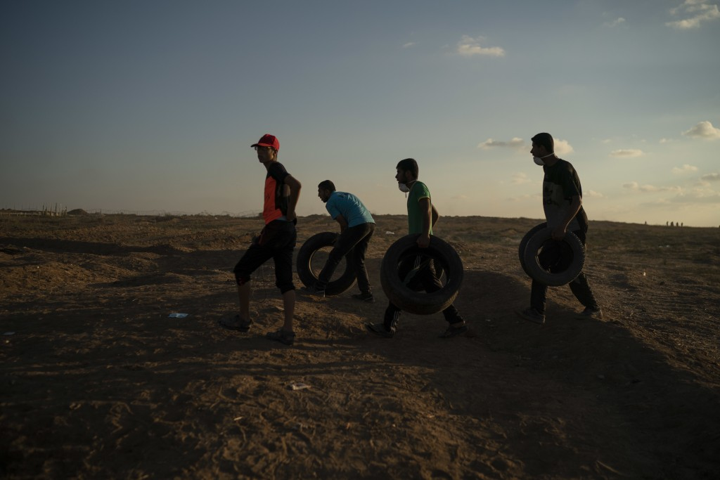 In this Friday, Sept. 14, 2018 photo, Palestinians roll tires toward the border fence to set them on fire during a protest at the Gaza Strip's border ...