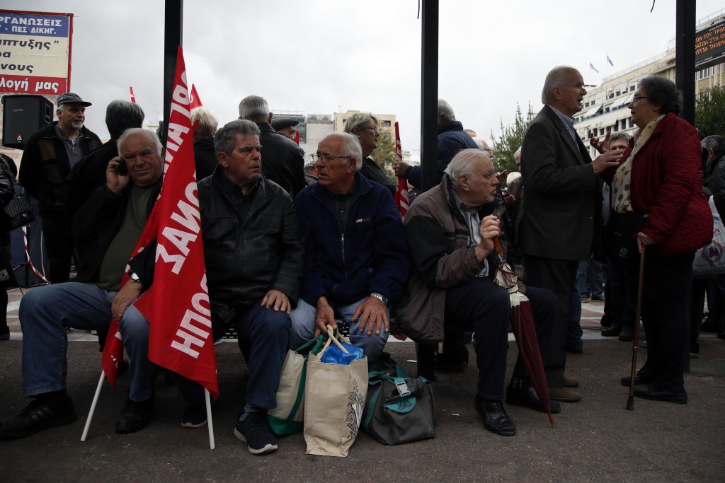 Elderly people sit on a bench during a rally in Athens, Tuesday, Nov. 20, 2018. Hundreds of pensioners protested demanding a return of funds lost as p