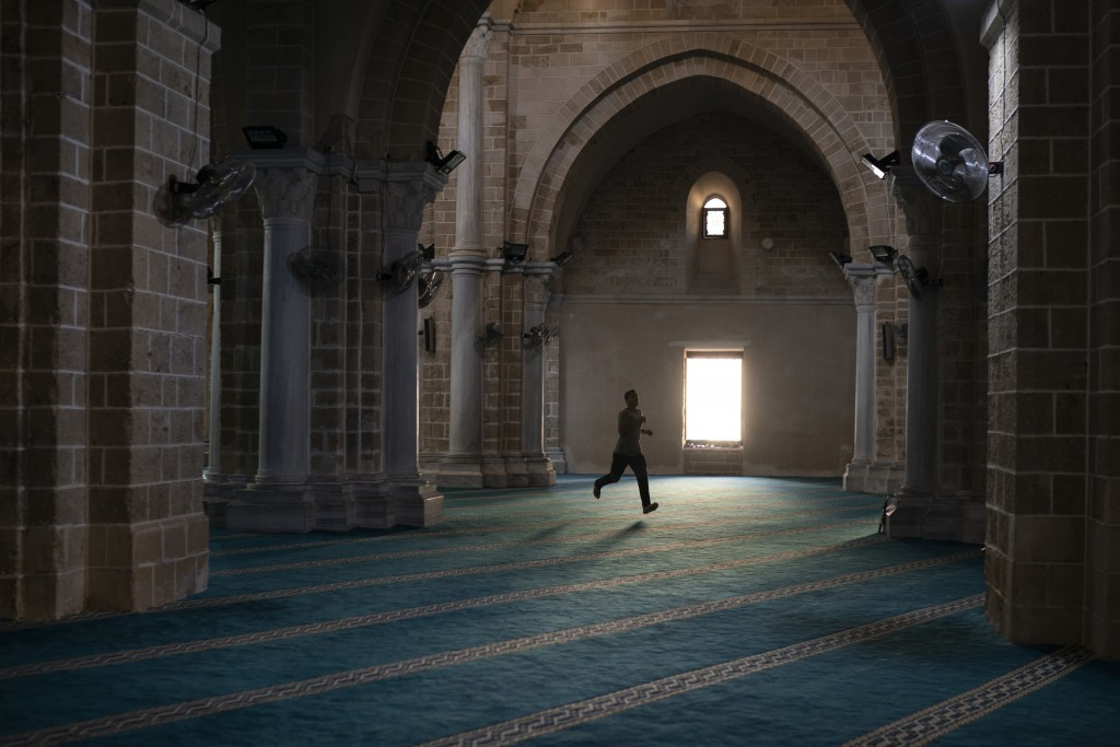 In this Friday, Sept. 14, 2018 photo, a man runs as he arrives a few minutes late for the afternoon prayer in a mosque in Gaza City. After Friday pray...