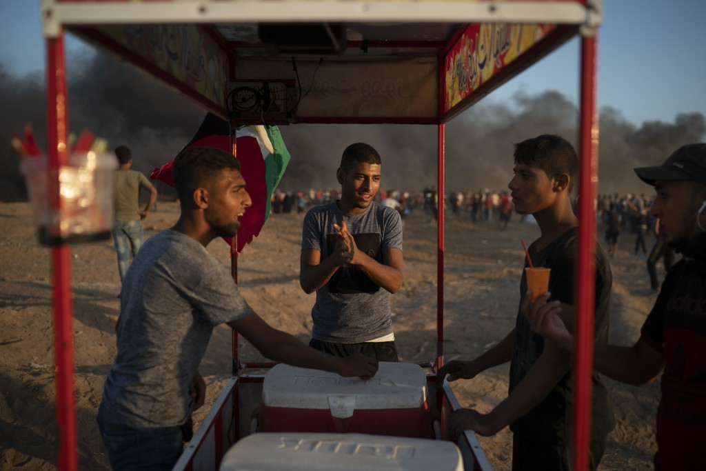 In this Friday, Sept. 14, 2018 photo, a vendor sells frozen drinks during a protest at the Gaza Strip's border with Israel, east of Gaza City. Eight m...