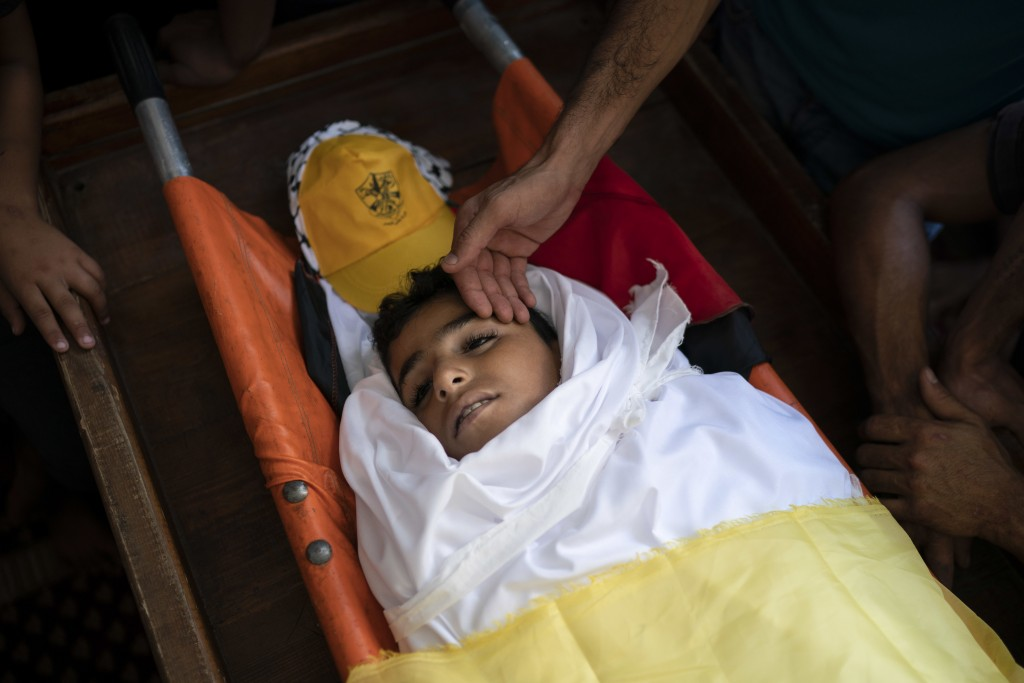 In this Sept. 15, 2018 photo, Palestinians mourn over the body of 11-year-old Shady Abdel-al during his funeral in Beit Lahiya, northern Gaza Strip. T...