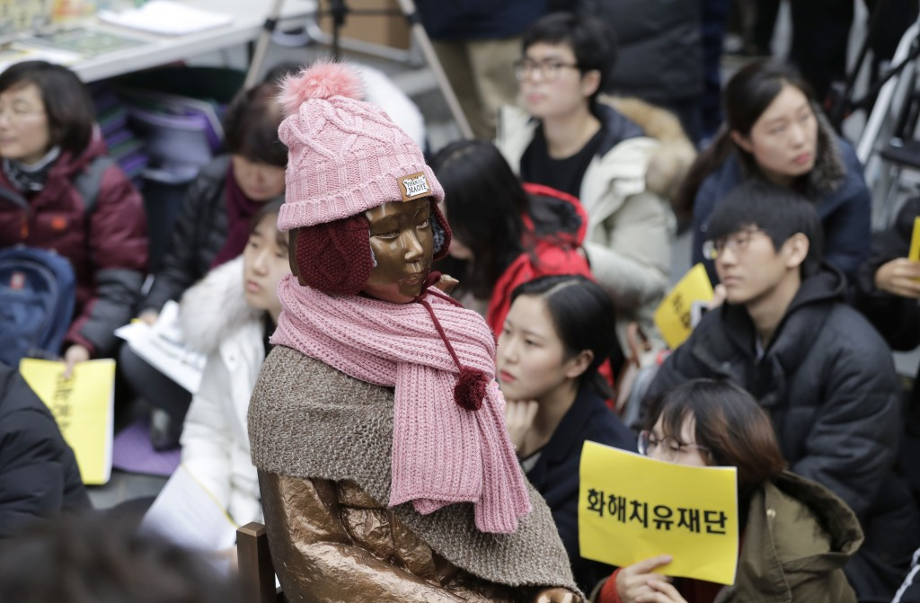 A statue of a girl representing thousands of Korean women enslaved for sex by Japan's imperial forces before and during World War II, is seen as parti