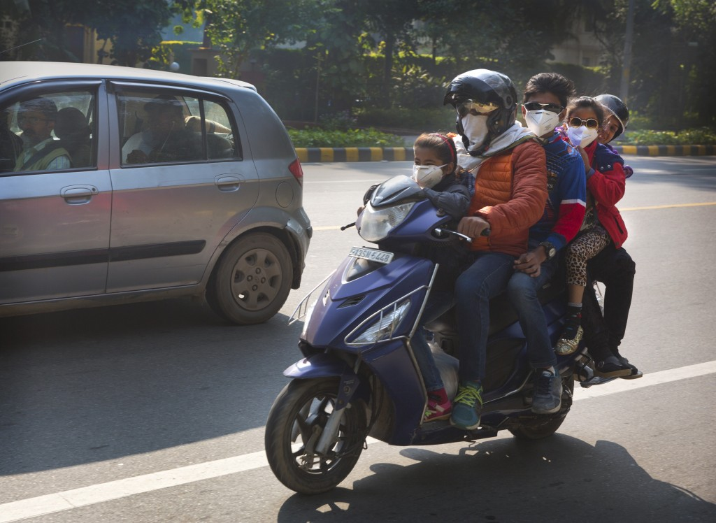 A family rides a scooter wearing pollution masks in New Delhi, India, Wednesday, Nov. 21, 2018. The Indian capital and large parts of north India suff