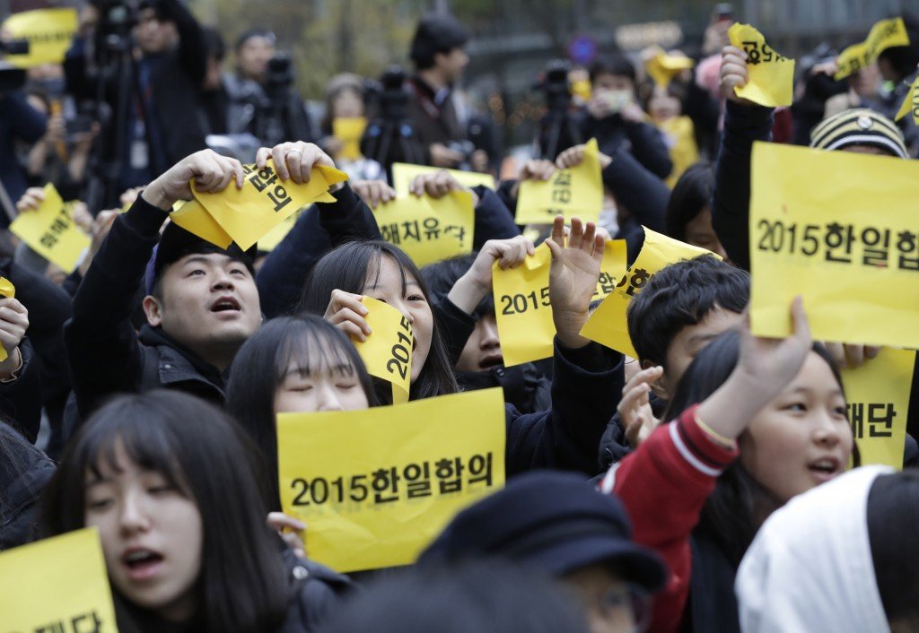 "Participants tear papers reading ""2015 agreement between South Korea and Japan"" during a weekly rally against Japanese government near the Japanese Em"