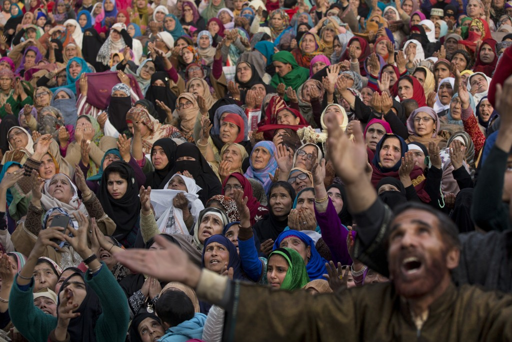 In this Nov. 21, 2018, photo, Kashmiri Muslims raise their hands in prayer as a head priest displays a relic of Prophet Muhammad at the Hazratbal shri...