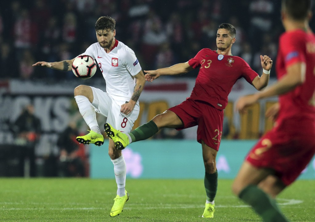 Portugal's Andre Silva vies for the ball with Poland's Mateusz Klich, left, during the UEFA Nations League soccer match between Portugal and Poland at