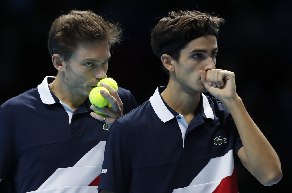 FILE - In this Wednesday, Nov. 14, 2018 file photo, Pierre-Hugues Herbert of France, right, and Nicolas Mahut of France talk tactics as they prepare t