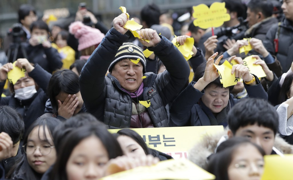 "Participants tear papers reading ""Reconciliation and Healing Foundation"" and ""2015 agreement between South Korea and Japan"" during a weekly rally agai"