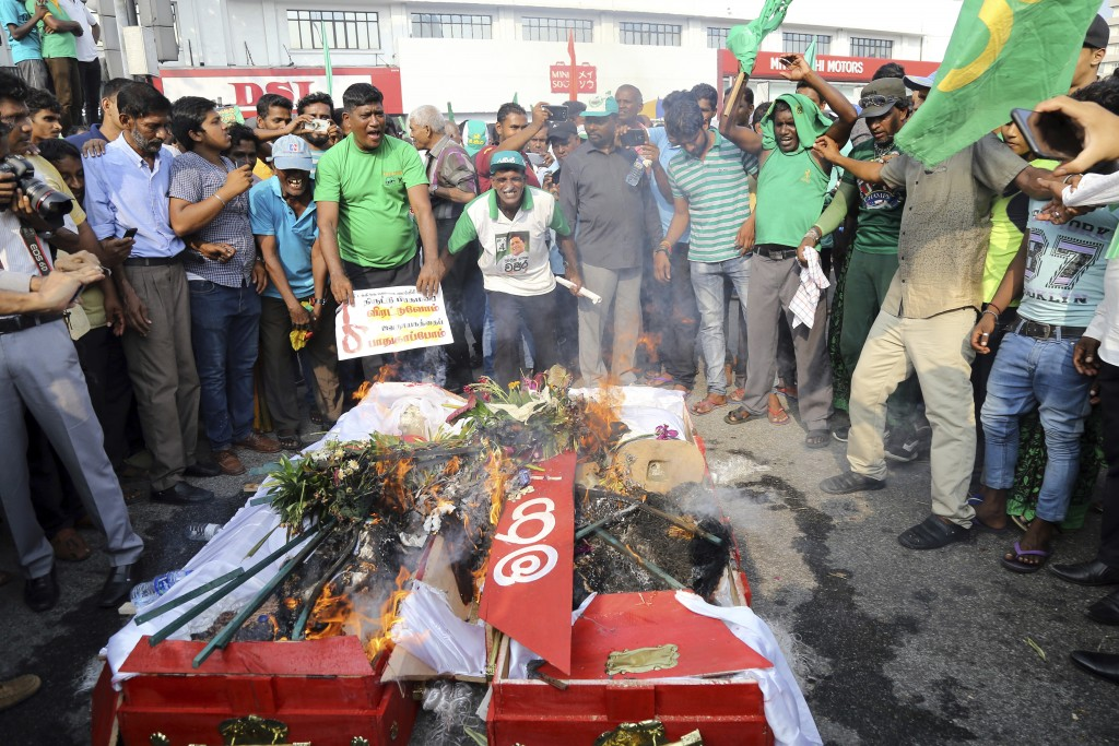 FILE - In this Nov. 15, 2018 file photo, supporters of the United National Party (UNP) and ousted Prime Minister Ranil Wickremesinghe burn coffins to ...