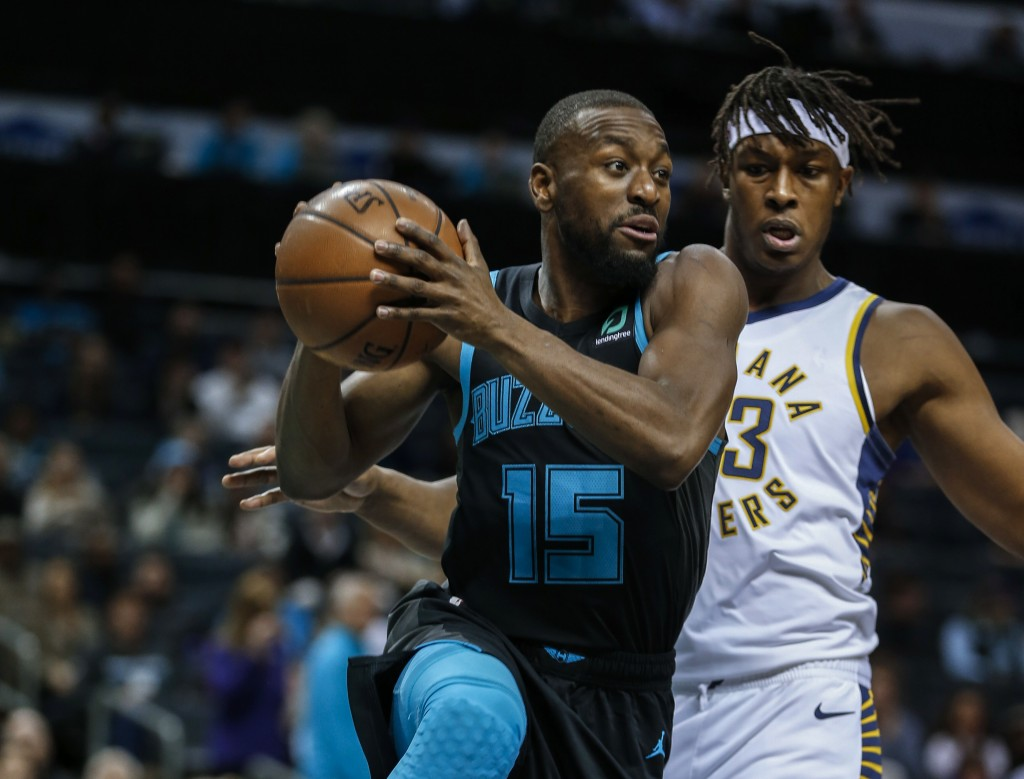 Charlotte Hornets guard Kemba Walker, left, looks to pass the ball as Indiana Pacers center Myles Turner defends during the first half of an NBA baske...