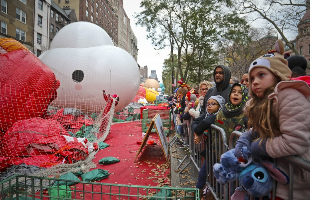 Crowds gather to see giant character balloons being inflated the night before their appearance in the 92nd Macy's Thanksgiving Day parade, Wednesday N...