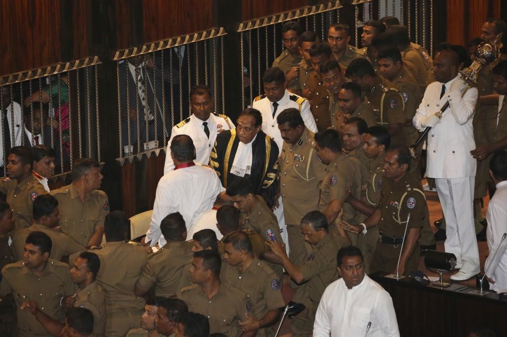 FILE - In this Nov. 16, 2018 file photo, policemen escort Speaker Karu Jayasuriya, in black robe, inside parliament in Colombo, Sri Lanka. Two men eac