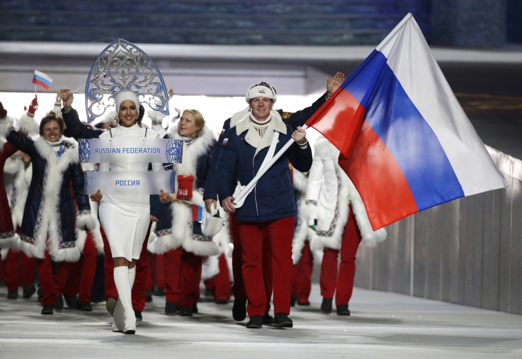 FILE - In this Feb. 7, 2014 file photo Alexander Zubkov of Russia carries the national flag as he leads the team during the opening ceremony of the 20