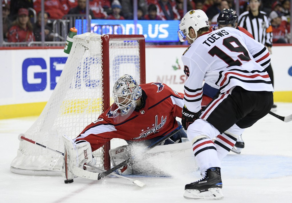 Washington Capitals goaltender Braden Holtby (70) reaches for the puck against Chicago Blackhawks center Jonathan Toews (19) during the second period ...
