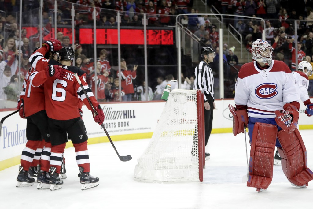 New Jersey Devils, left, celebrate a goal by center Pavel Zacha (37) as Montreal Canadiens goaltender Carey Price, right, skates away during the secon...