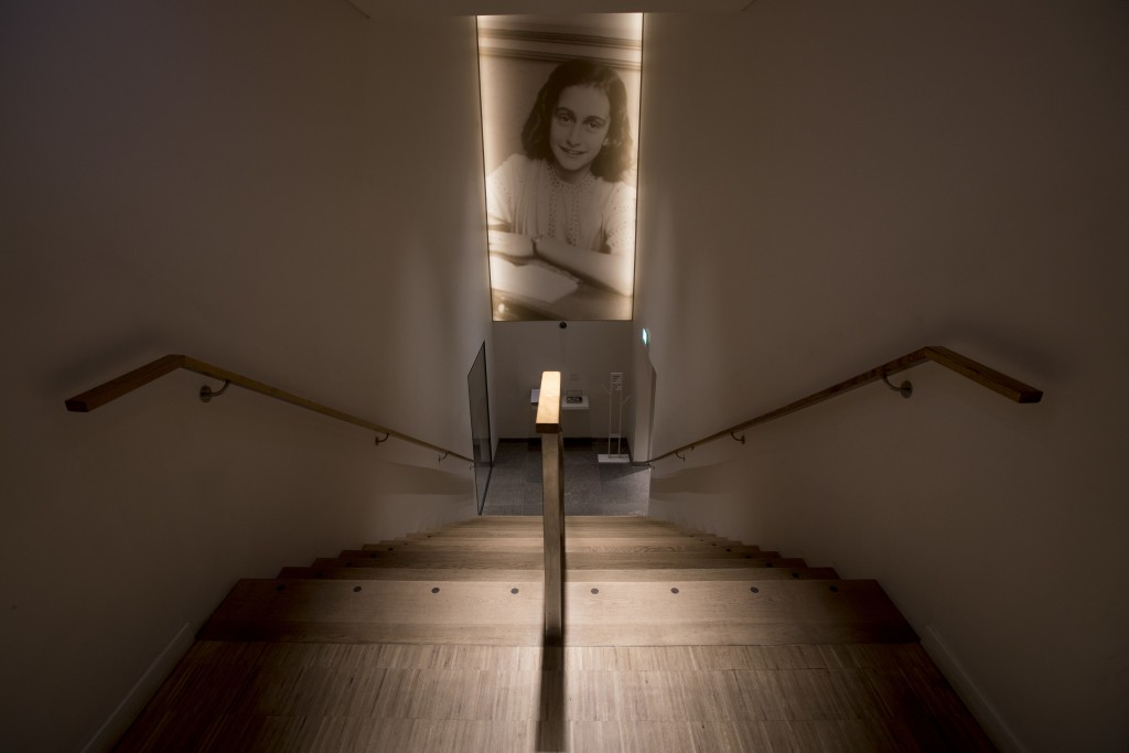 A picture of Anne Frank accompanies visitors as they leave the renovated Anne Frank House Museum in Amsterdam, Netherlands, Wednesday, Nov. 21, 2018. ...