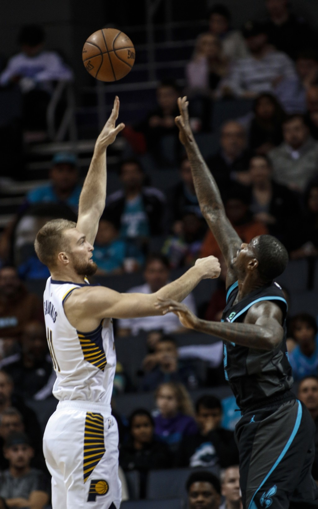Indiana Pacers forward Damantas Sabonis, left, shoots over Charlotte Hornets forward Marvin Williams during the first half of an NBA basketball game i