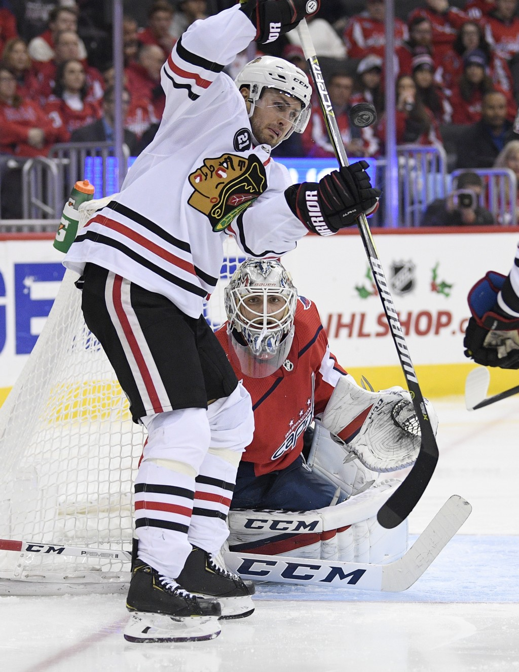 Chicago Blackhawks center Marcus Kruger, front, watches the puck in front of Washington Capitals goaltender Braden Holtby, back, during the second per