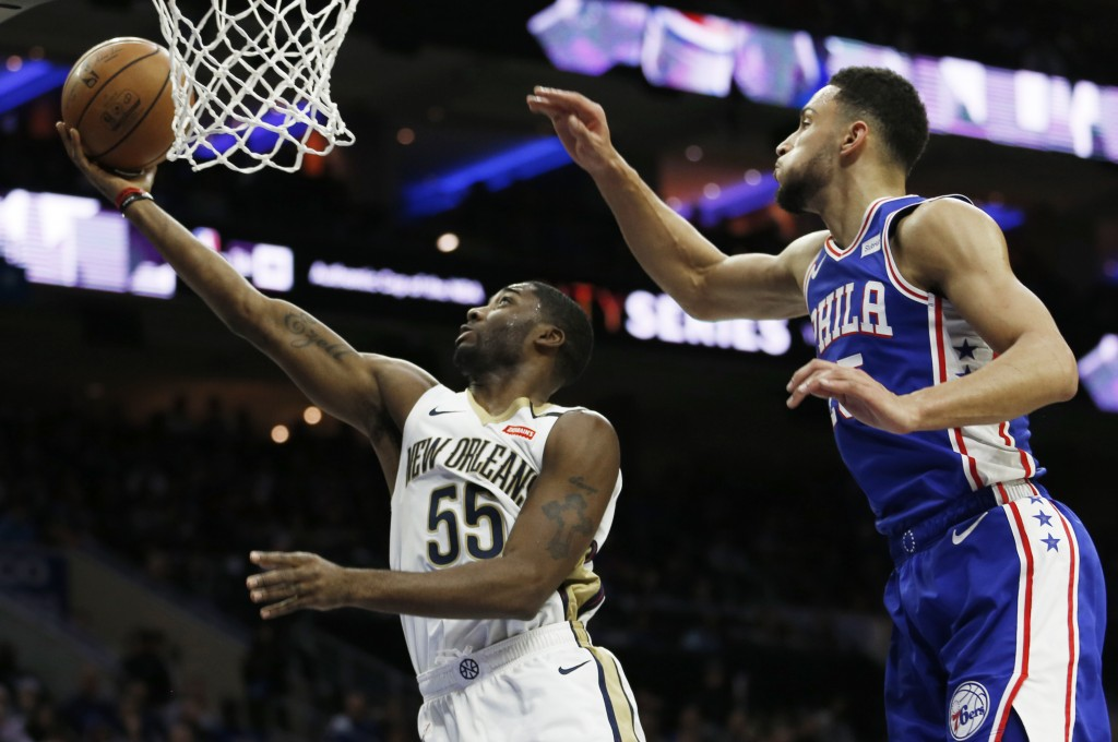 New Orleans Pelicans guard E'Twaun Moore (55) takes a shot followed by Philadelphia 76ers guard Ben Simmons (25) in the first half on an NBA basketbal...