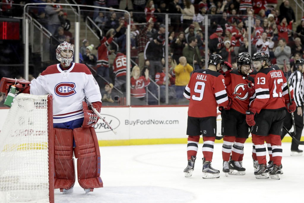 Montreal Canadiens goaltender Carey Price, left, stands near his net after allowing a goal to New Jersey Devils left wing Taylor Hall (9) during the s...