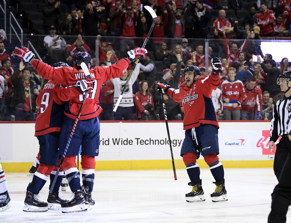 Washington Capitals right wing Tom Wilson (43) celebrates his goal with center Nicklas Backstrom (19), of Sweden, and left wing Alex Ovechkin (8), of
