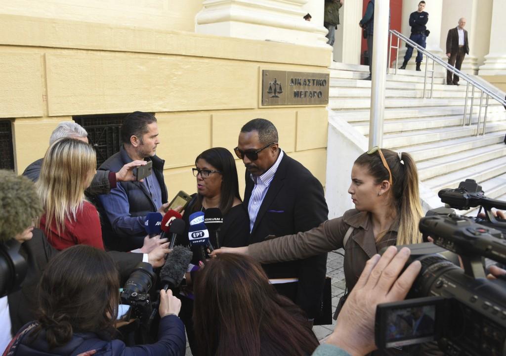 Phil and Jill Henderson, center, parents of Bakari Henderson, face the media outside the court house in Patras, Greece, on Thursday, Nov. 22, 2018. A