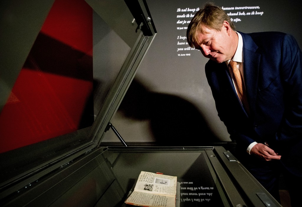 Dutch King Willem-Alexander looks at Anne Frank's diary, foreground, displayed in the new Diary Room at the renovated Anne Frank House Museum in Amste...