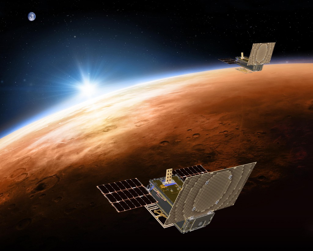 FILE - This illustration made available by NASA in March 2018 shows the twin Mars Cube One project (MarCO) spacecrafts flying over Mars with Earth and...