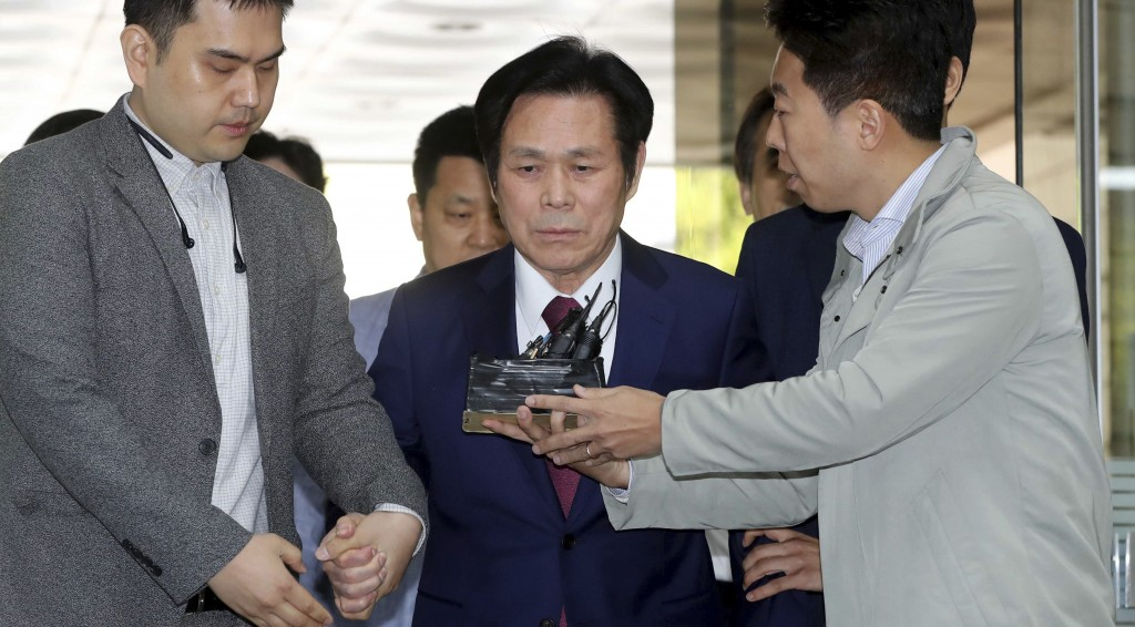 In this May 3, 2018 photo, A South Korean pastor Lee Jae-rock, center, is questioned by reporters upon his arrival for hearing at the Seoul Central Di...