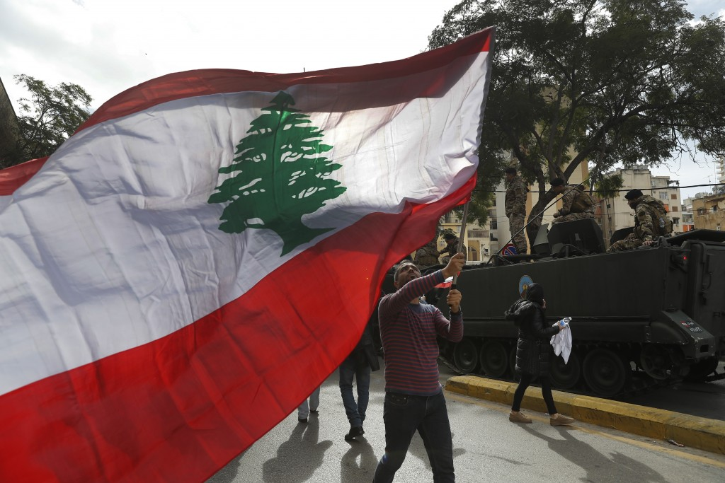 A protester waves a Lebanese flag during a protest against corruption and the failure of long-serving politicians to form a government, in Beirut, Leb...
