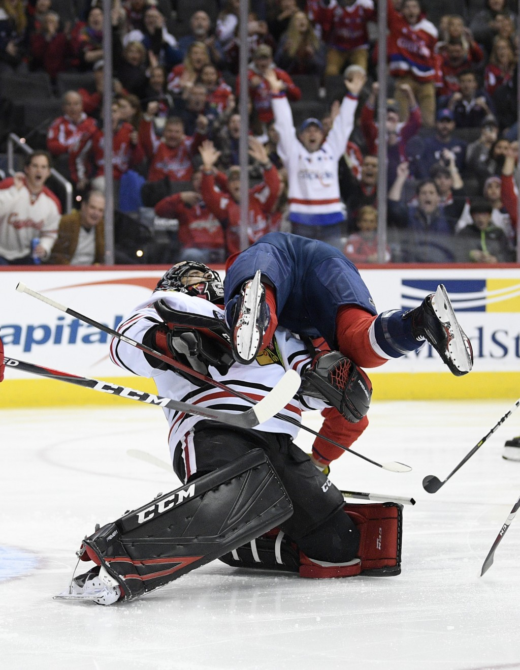 Washington Capitals right wing Tom Wilson, top, collides with Chicago Blackhawks goaltender Corey Crawford, bottom, after he scored a goal during the