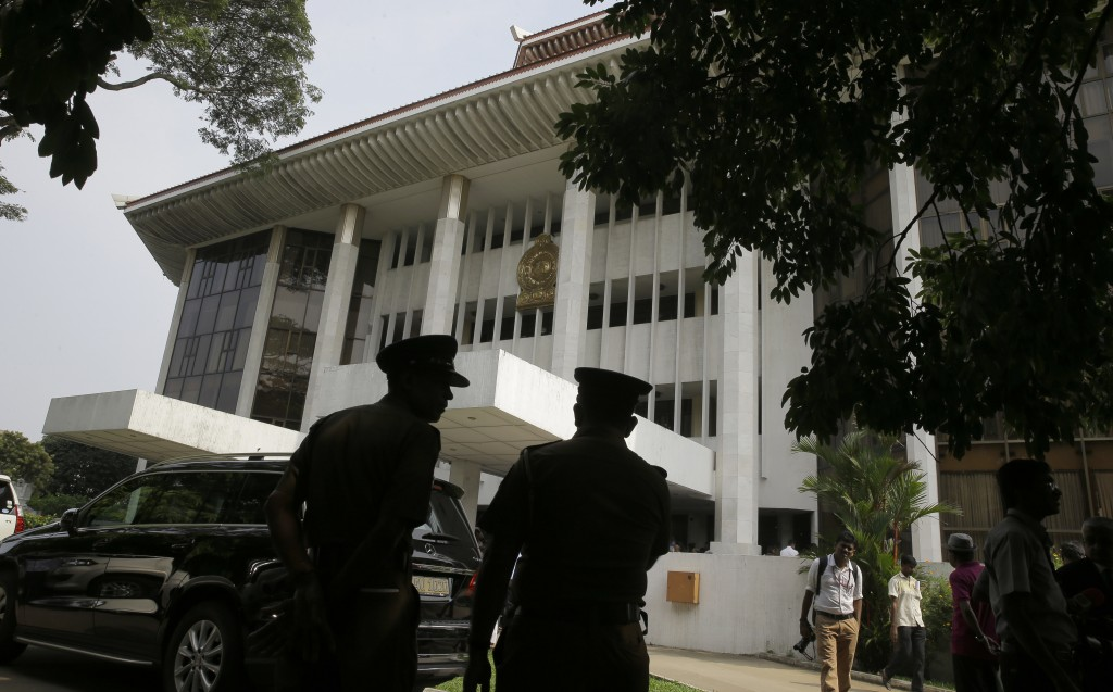 FILE - In this Nov. 12, 2018 file photo, Sri Lankan police officers stand guard outside the supreme court complex in Colombo, Sri Lanka. Two men each
