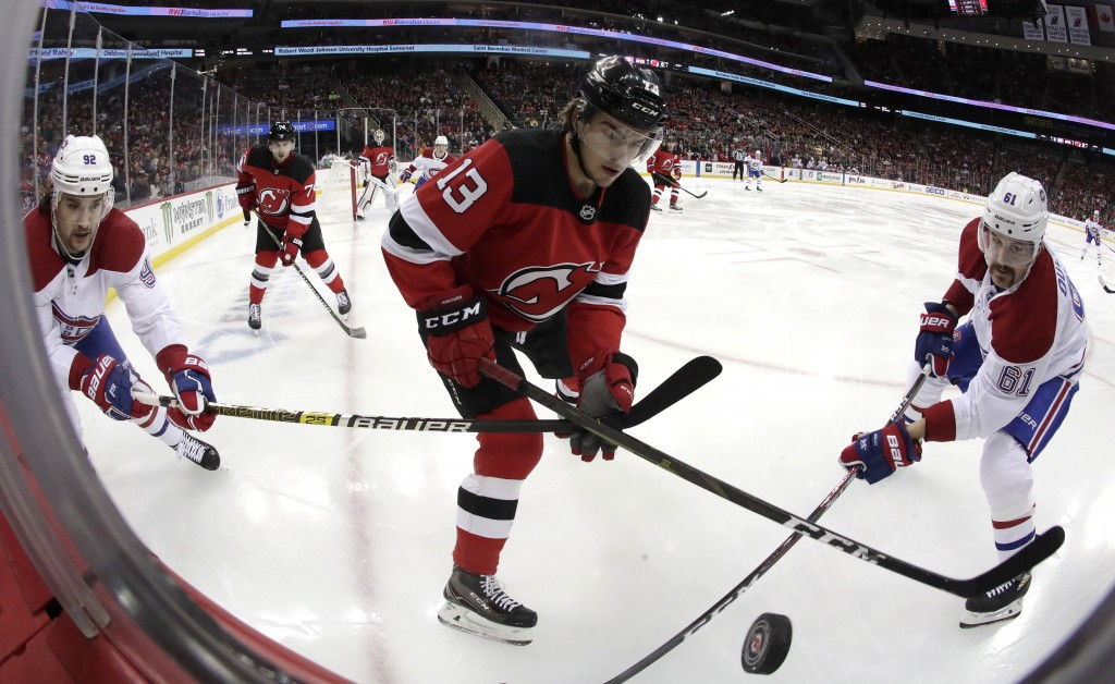 New Jersey Devils center Nico Hischier (13), of Switzerland, competes for the puck with Montreal Canadiens center Jonathan Drouin (92) and defenseman ...