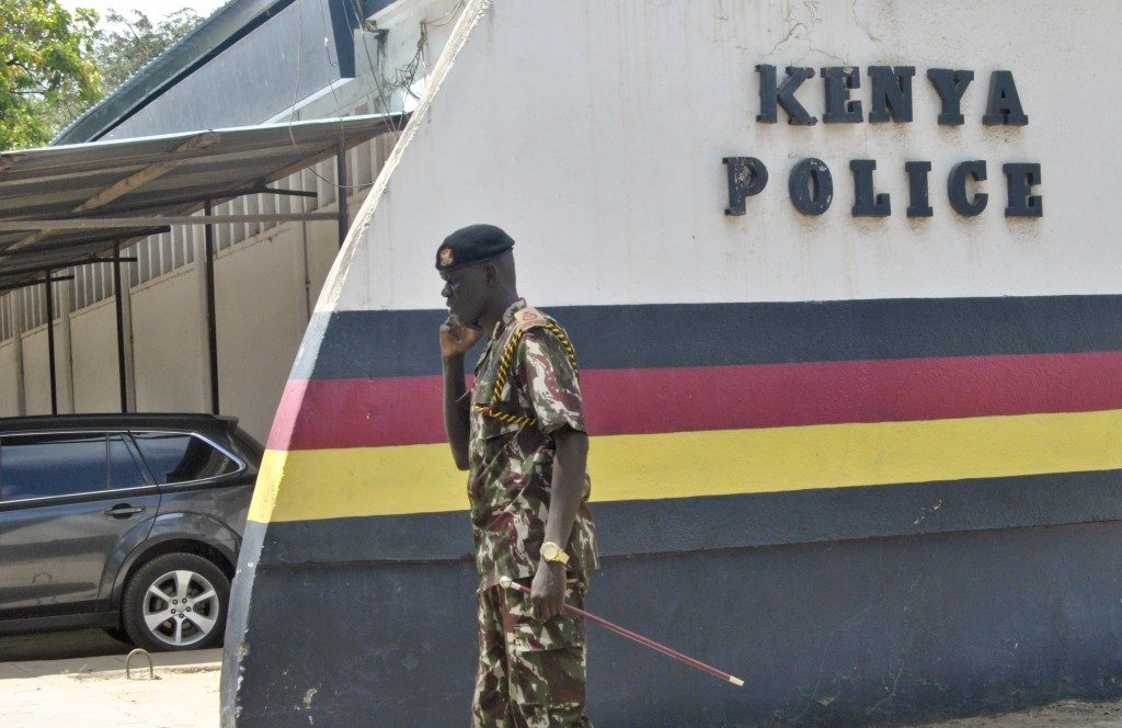 A Kenyan police officer talks on his phone inside the compound of the command centre that is directing operations in the search for kidnapped Italian