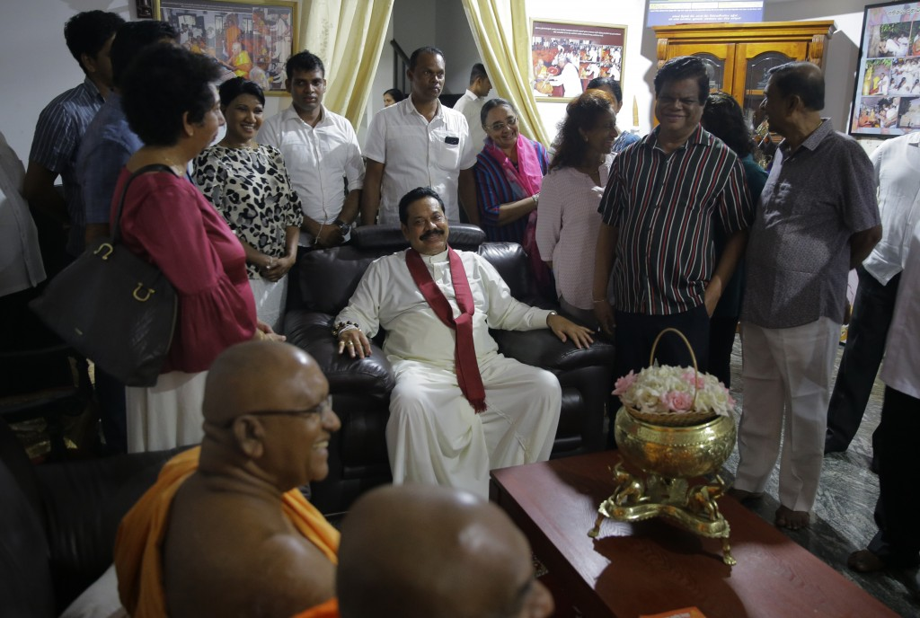 FILE - In this Oct. 26, 2018 file photo, newly appointed Sri Lankan Prime Minister Mahinda Rajapaksa, center, sits to talk with supporters at a Buddhi