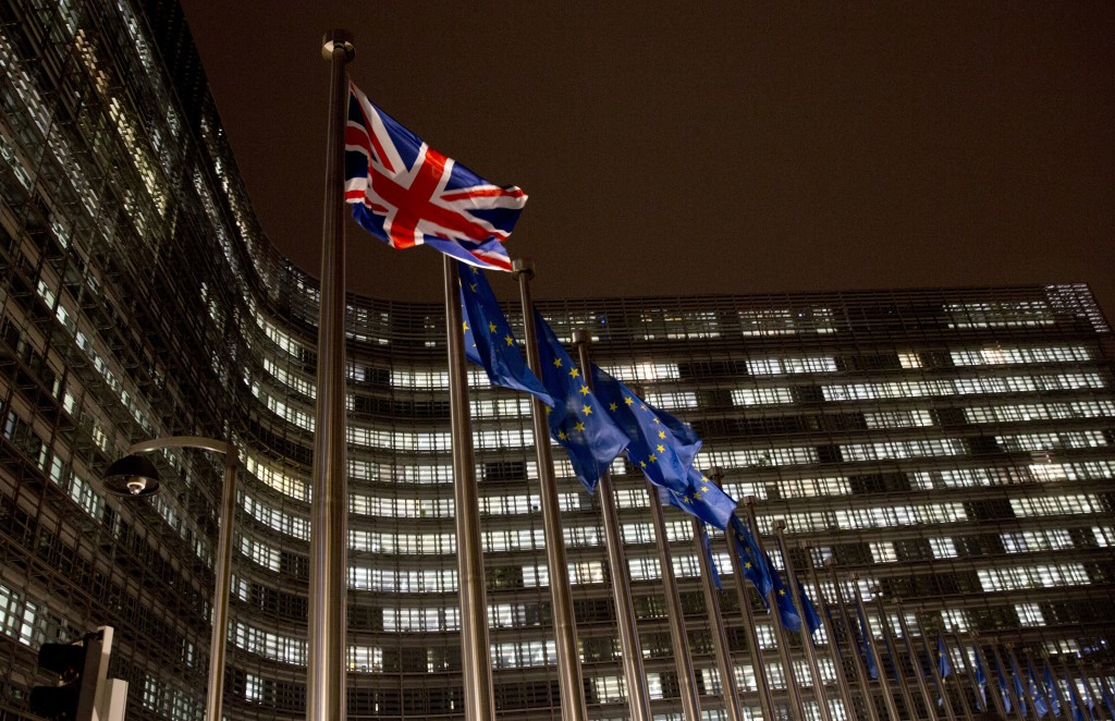A Union flag, left, flaps in the wind alongside EU flags in front of European Commission headquarters in Brussels, Wednesday, Nov. 21, 2018. British P