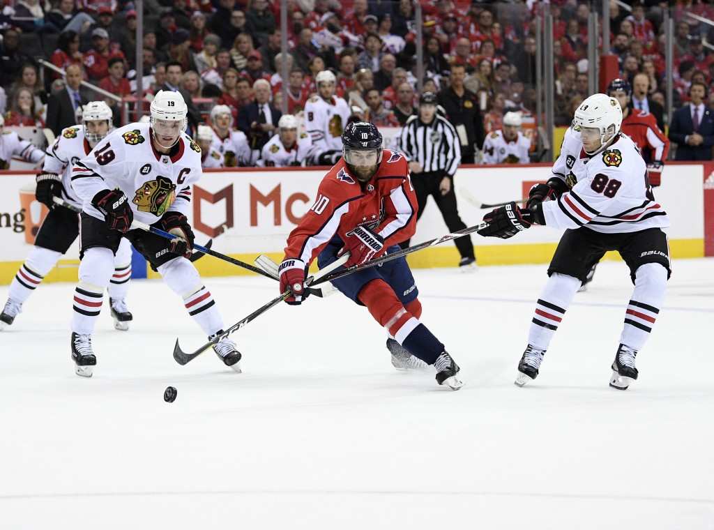 Chicago Blackhawks right wing Patrick Kane (88) and center Jonathan Toews (19) battle for the puck against Washington Capitals right wing Brett Connol