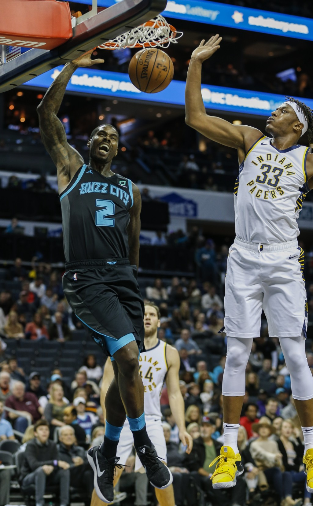 Charlotte Hornets forward Marvin Williams, left, dunks next to Indiana Pacers center Myles Turner during the first half of an NBA basketball game in C...