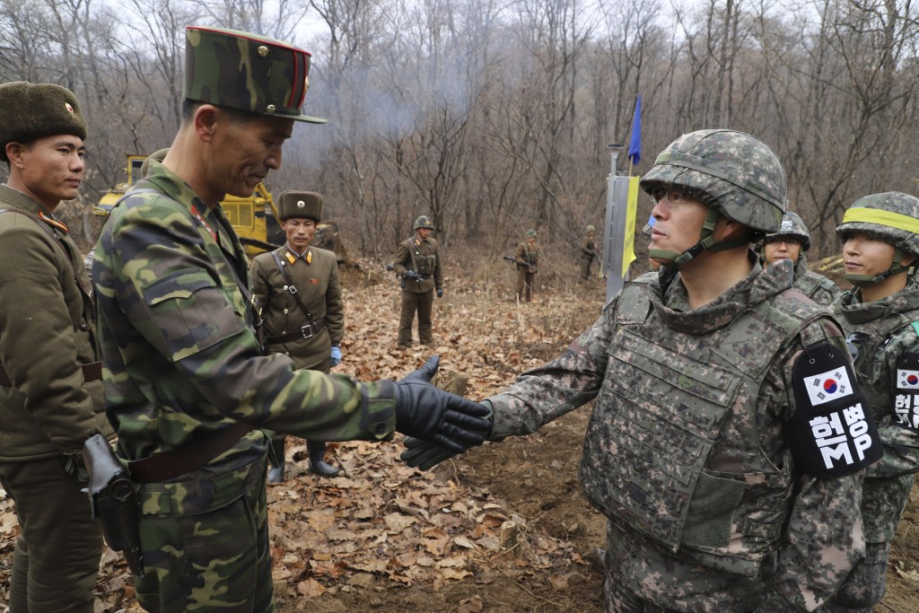 In this undated photo provided on Nov. 22, 2018, by South Korea Defense Ministry, a South Korean soldier, right, and North Korean soldier, left, shake...
