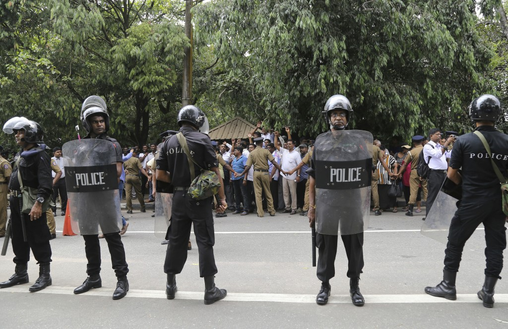FILE - In this Nov. 14, 2018 file photo, Sri Lankan riot policemen stand between supporters of ousted Prime Minister Ranil Wickremesinghe and supporte